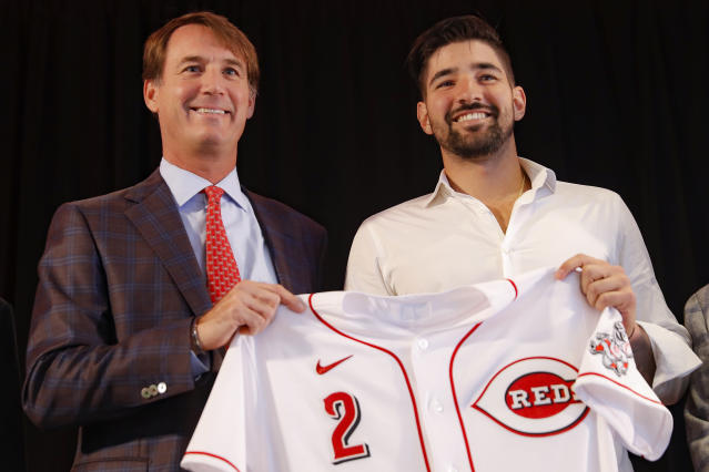 Cincinnati Reds' Nick Castellanos, right, holds his jersey alongside Reds president and director of operations Dick Williams during a news conference, Tuesday, Jan. 28, 2020, in Cincinnati. Castellanos signed a $64 million, four-year deal with the baseball club. (AP Photo/John Minchillo)