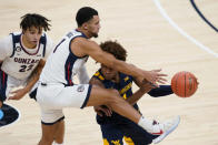 West Virginia's Miles McBride (4) makes a pass while being defended by Gonzaga's Jalen Suggs (1) during the first half of an NCAA college basketball game Wednesday, Dec. 2, 2020, in Indianapolis. (AP Photo/Darron Cummings)