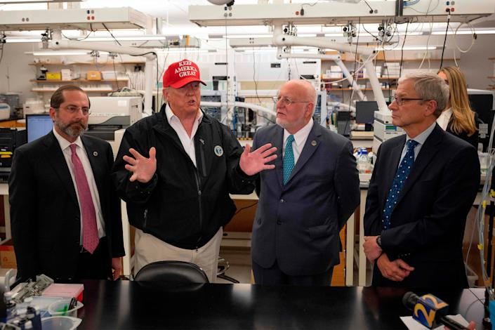 US President Donald Trump (2nd L) speaks next to US Health and Human Service Secretary Alex Azar (L), CDC Director Robert Redfield (2nd R), and CDC Associate Director for Laboratory Science and Safety (ADLSS) Dr. Steve Monroe during a tour of the Centers for Disease Control and Prevention (CDC) in Atlanta, Georgia, on March 6, 2020.