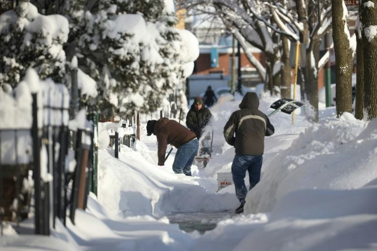 Residents clear snow from a sidewalk on February 16, 2021 in Chicago, Illinois