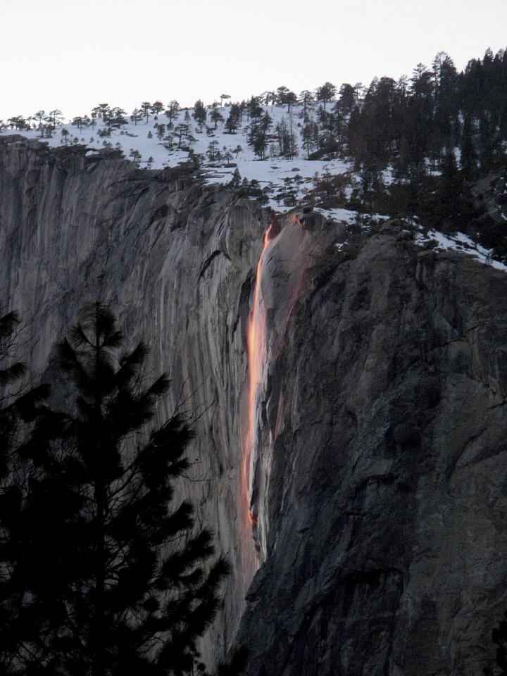 In this undated handout photo provided by the Scott Gediman of the Yosemite National Park Service, the firefall from Glacier Point is shown in Yosemite. A window of time just opened in Yosemite National Park when nature photographers wait, as if for an eclipse, until the moment when the sun and earth align to create a fleeting phenomenon. This marvel of celestial configuration happens in a flash at sunset in mid-February _ if the winter weather cooperates. On those days the setting sun illuminates one of the park's lesser-known waterfalls so precisely that it resembles molten lava as it flows over the sheer granite face of the imposing El Capitan. (AP Handout Photo/Yosemite National Park Service, Bethany Gediman) MUST CREDIT NATIONAL PARK SERVICE