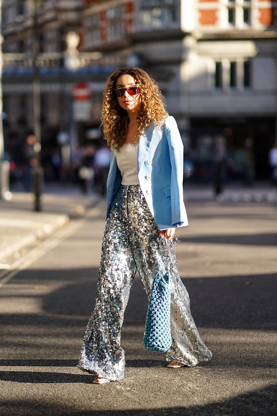 Yasmine Daas is seen wearing a pale blue blazer and shiny sequinned flared trousers. [Photo: Getty Images]