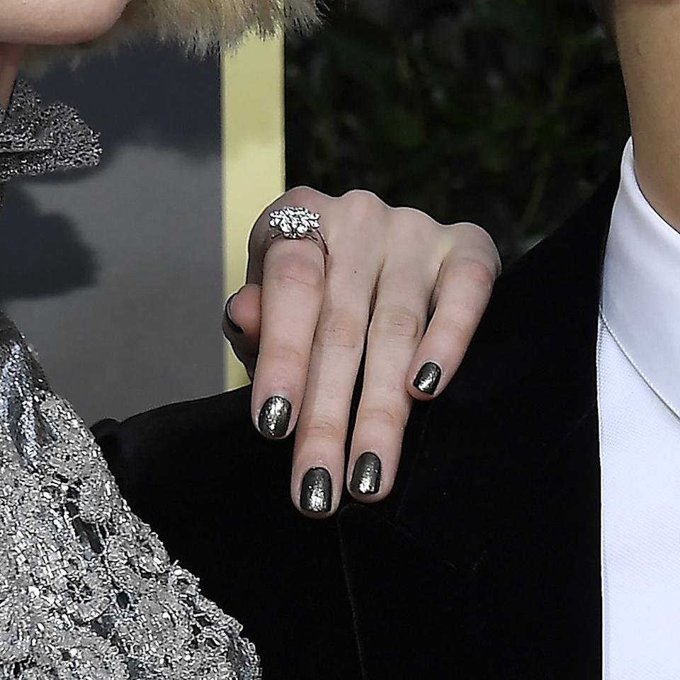 "Manicurist Mel Shangaris kept Lucy Boynton's nails simple yet edgy to match her <a href=""https://www.allure.com/story/golden-globes-2020-lucy-boynton-sparkly-eyeliner-exclusive?mbid=synd_yahoo_rss"">graphic black eye makeup</a>. After applying a base of Chanel lacquer in Pure Black, she dusted on a thin coat of metallic silver eye shadow before sealing it all with a shiny top coat."