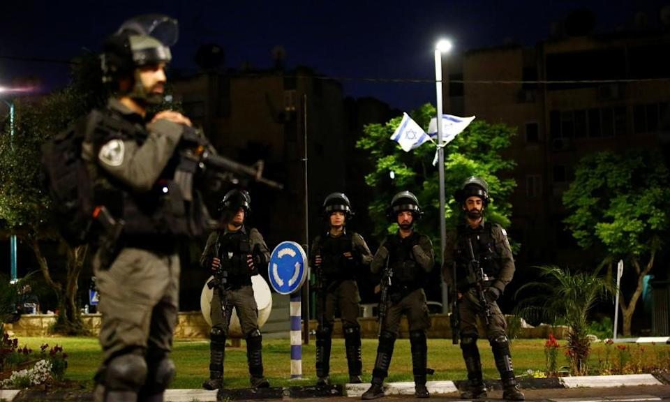 Israeli border police force members stand by one of the entrances to the Arab-Jewish town of Lod, Israel.