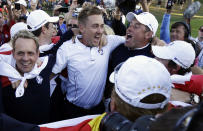 Europe's Luke Donald, , left, Ian Poulter, center, Lee Westwood and Rory McIlroy, obscured at far right, celebrate after winning the Ryder Cup PGA golf tournament at the Medinah Country Club in Medinah, Ill., in this Sunday, Sept. 30, 2012, file photo. (AP Photo/David J. Phillip, File)