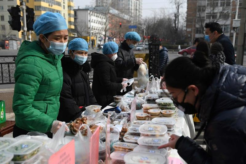 Restaurant workers wear face masks as a preventive measure against the COVID-19 coronavirus as they sell packaged meals in a car park outside their restaurant in Beijing on Feb. 21, 2020.