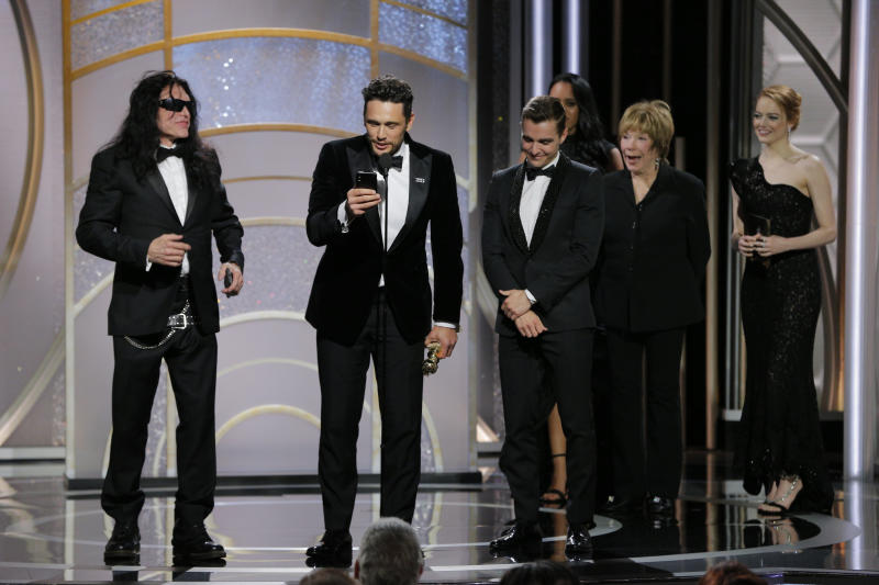 """In this handout photo provided by NBCUniversal, James Franco, with Tommy Wiseau and Dave Franco, accepts the award for Best Performance by an Actor in a Motion Picture – Musical or Comedy for """"The Disaster Artist"""" during the 75th Annual Golden Globe Awards at The Beverly Hilton Hotel on January 7, 2018 in Beverly Hills, California"""
