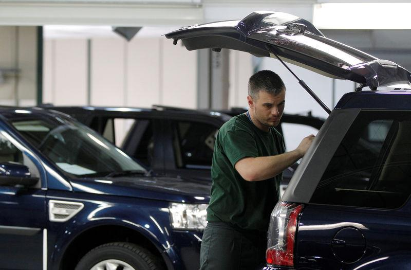 FILE PHOTO: Workers examine Land Rover Freelander vehicles as they come off the production line at Jaguar Land Rover's Halewood assembly plant in Liverpool