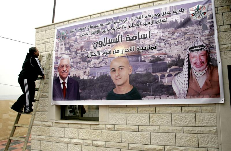 "A Palestinian relative of Osama Al-Selawai hangs a poster with his picture in the middle, with pictures of Palestinian President, Mahmoud Abbas, left, and former President Yasser Arafat, right, at Al-Selawai's home in the West Bank city of Jenin, Monday, Dec. 30, 2013. Al-Selawai is one of 26 long-serving Palestinian prisoners who were convicted in connection to the killing of Israelis, that Israel announced it will release this week under a U.S.-brokered formula to resume Mideast peace talks. Arabic reads, ""Jenin municipality and the Palestinian National Liberation Movement - Fatah (Jenin city), congratulates Jenin son, the free prisoner, Osama Al-Selawai, for his freedom from the shackles of occupation."" (AP Photo/Mohammed Ballas)"