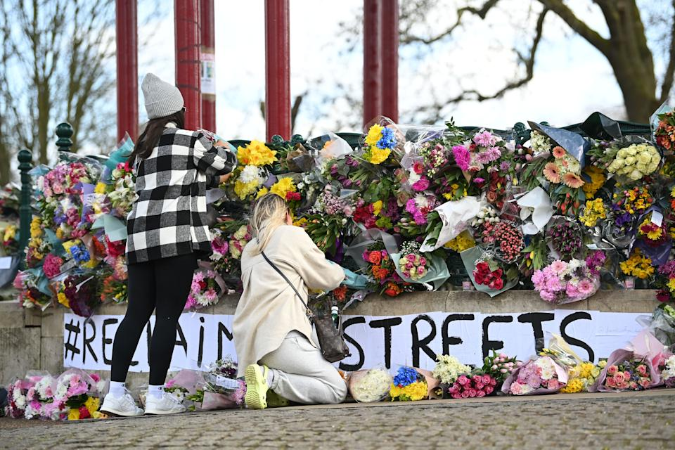 LONDON, ENGLAND - MARCH 13: Two women leave tributes for Sarah Everard at the bandstand on Clapham Common on March 13, 2021 in London, United Kingdom.  Vigils are being held across the United Kingdom in memory of Sarah Everard. Yesterday, the Police confirmed that the remains of Ms Everard were found in a woodland area in Ashford, a week after she went missing as she walked home from visiting a friend in Clapham. Metropolitan Police Officer Wayne Couzens has been charged with her kidnap and murder. (Photo by Leon Neal/Getty Images)