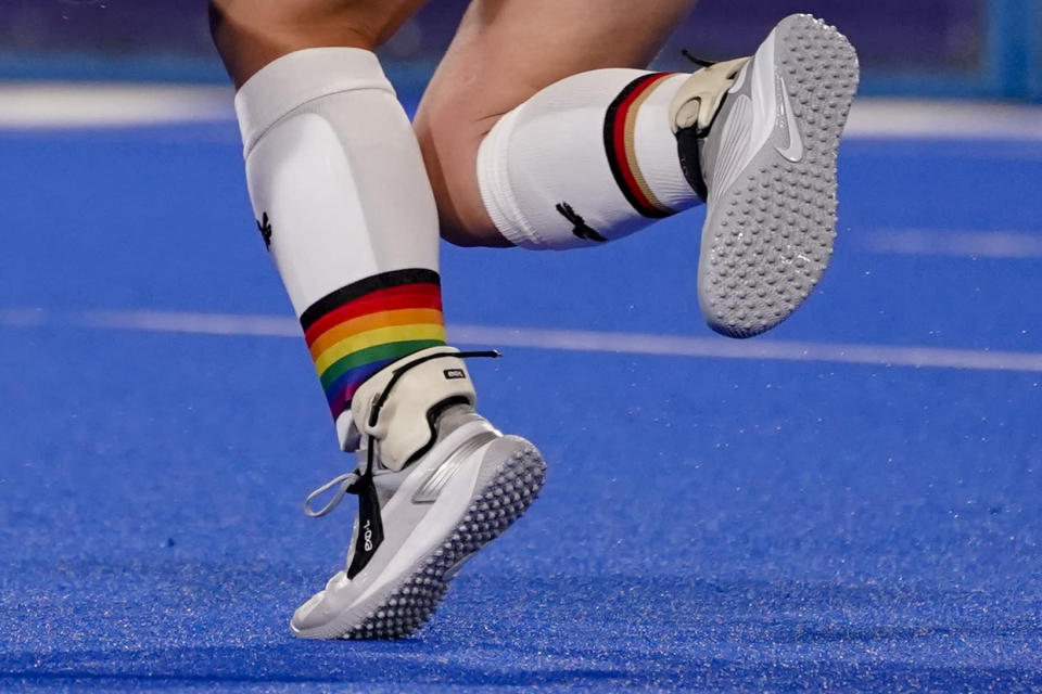 Germany's Nike Lorenz wears a rainbow emblazoned shin guard as she passes the ball during a women's field hockey match against India at the 2020 Summer Olympics, Monday, July 26, 2021, in Tokyo, Japan. (AP Photo/John Minchillo)