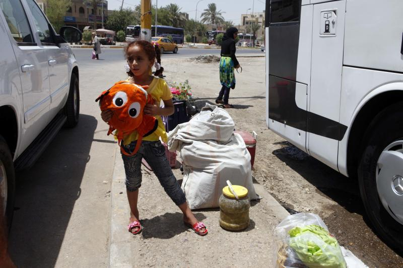 Layla Fadhil, an Iraqi refugee, stands with her family's belongings after her arrival from Syria to the Mansour neighborhood of Baghdad, Iraq, Friday, July 20, 2012. Iraq has flown hundreds of its citizens out of Damascus to escape the civil war in Syria, an official said Friday, while thousands of Iraqis poured through a major border crossing despite rebel takeovers of Syrian government posts and escalating violence near the two nations??? boundaries. (AP Photo/Karim Kadim)