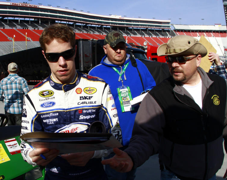 NASCAR Sprint Cup driver Brad Keselowski, left, signs an autograph prior to practice the Food City 500 auto race, Friday, March 15, 2013, in Bristol, Tenn. The race will be run on Sunday. (AP Photo/Wade Payne)