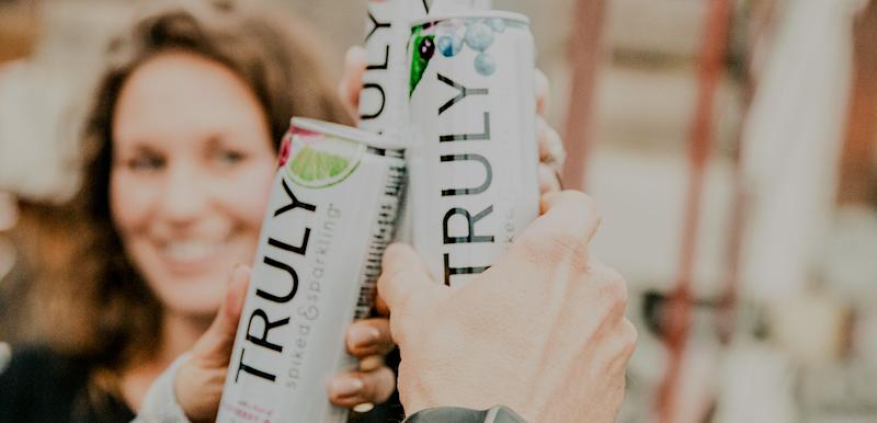 Woman toasting with can of Truly hard seltzer