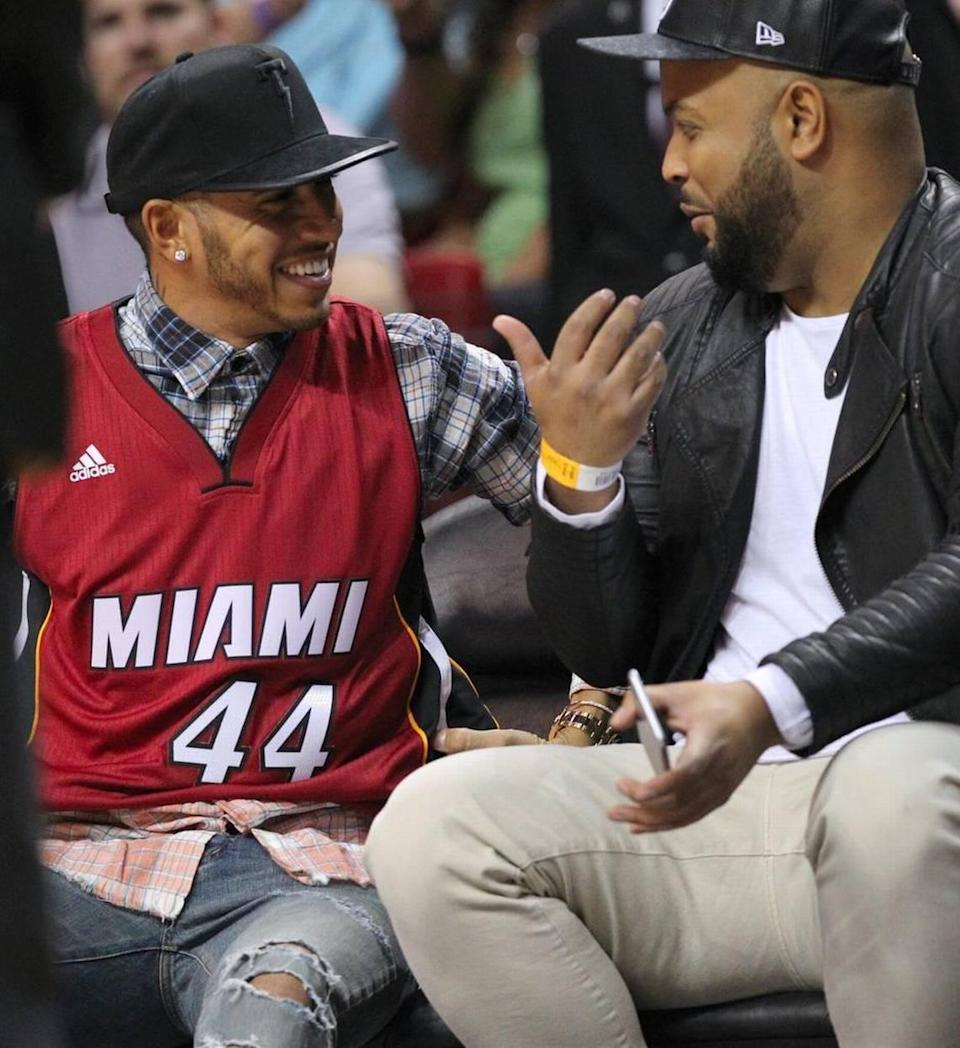 British Formula One racing driver Lewis Hamilton wearing Heat jersey with his car No. 44 during a Miami Heat game at AmericanAirlines Arena on New Year's Day, 2016. The only Black driver in F1 history has won the World Championship seven times, tying Germany's Michael Schumacher for the most ever, and holds the career records for wins and pole positions.