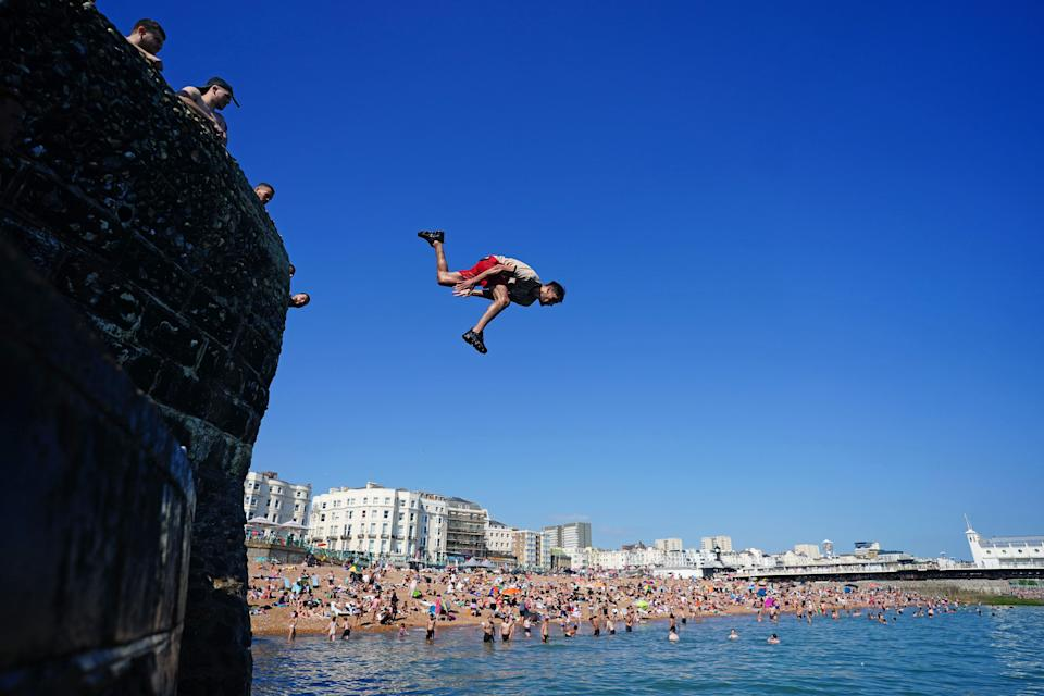 People jump into the sea from a groyne at Brighton beach in East Sussex (Victoria Jones, PA) (PA Wire)