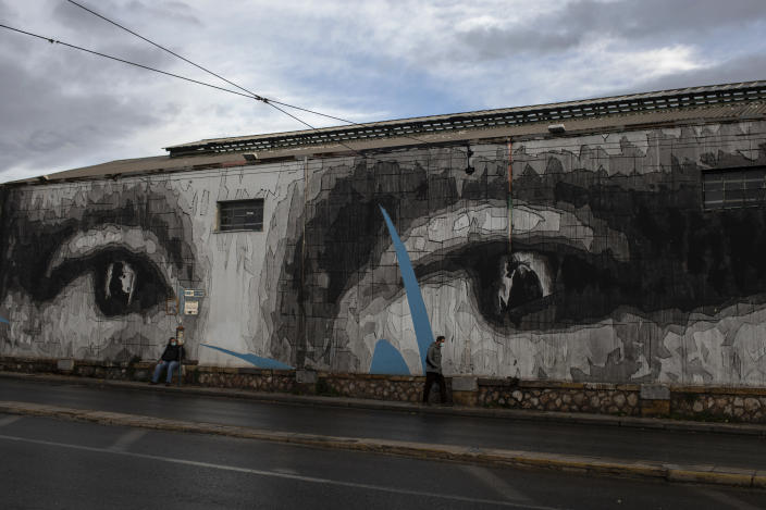 Two men wearing face masks to prevent the spread of the coronavirus walk past a giant mural by Greek street artist iNO depicting the eyes of Leonardo da Vinci's Mona Lisa, in Athens, Thursday, Dec. 10, 2020. Greece is expected to see a 10.5% contraction of its gross domestic product this year, above the forecasted EU average of 7.4%, while its debt-to-GDP ratio is set to surge to a staggering 208.9% according to the EU and Greek authorities. (AP Photo/Petros Giannakouris)