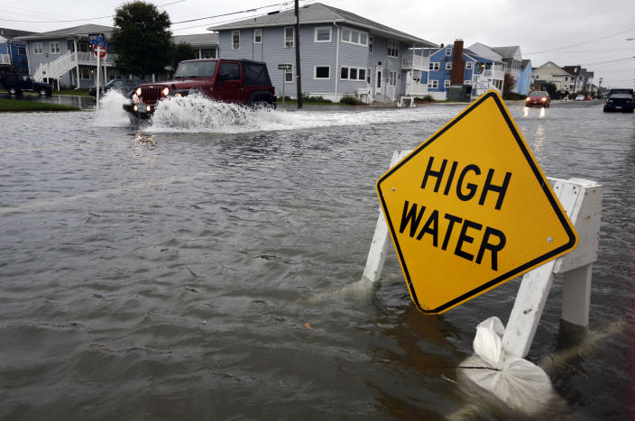 A car goes through the high water as Hurricane Sandy bears down on the East Coast, Sunday, Oct. 28, 2012, in Ocean City, Md. Governors from North Carolina, where steady rains were whipped by gusting winds Saturday night, to Connecticut declared states of emergency. Delaware ordered mandatory evacuations for coastal communities by 8 p.m. Sunday. (AP Photo/Alex Brandon)