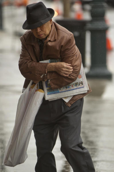 A pedestrian faces the rainy weather in the Chinatown district of Los Angeles on Friday, April 13, 2012. A powerful spring storm that zapped an airliner with lighting in San Francisco moved across California on Friday, threatening the state with thundershowers, fierce winds and blinding snow flurries in the mountains. (AP Photo/Damian Dovarganes)