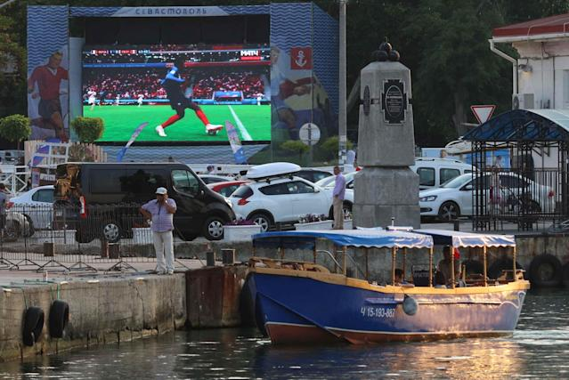 Soccer Football - World Cup - Group C - France vs Peru - Sevastopol, Crimea - June 21, 2018 A boat is seen in front of an electronic screen showing a live broadcast of the match at the Artillery Bay waterfront. REUTERS/Pavel Rebrov