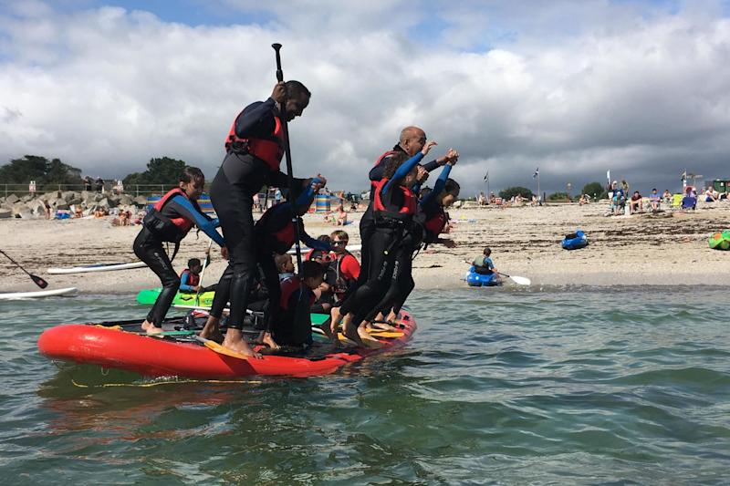 People paddle boarding, as survivors of the Grenfell Tower fire enjoyed a week-long group holiday in Cornwall: PA