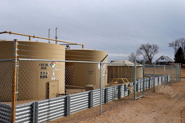 A crude oil storage tank behind a fence near Mead, Colo, in 2017. (Photo: Brennan Linsley/AP)
