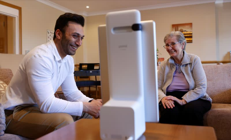 Resident Tolson chats via Facebook Portal to her family, helped by estate manager Gandecha at the Foxholes Care Home