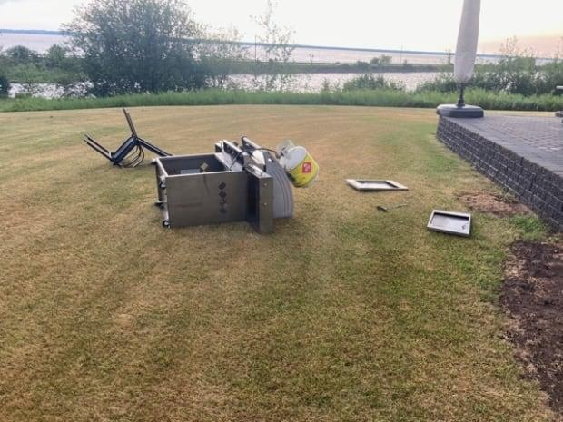 Debbie Rizzoli's barbecue and much of her yard was torn up by the wind and storm that came through Saturday evening.  (Submitted by Debbie Rizzoli - image credit)