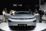FILE PHOTO: People look at XPeng's P7 sedan model displayed at the Guangzhou auto show in Guangzhou