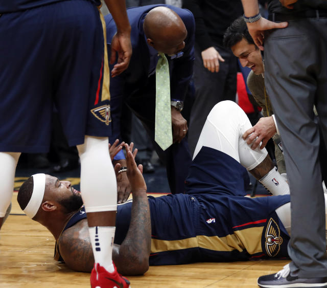 Pelicans center DeMarcus Cousins lies on the court while being tended to after injuring his left Achilles tendon Friday night. (AP)