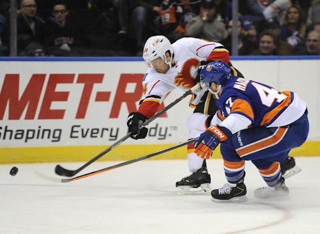 Calgary Flames' David Jones (54) shoots the puck towards the net ahead of New York Islanders' Andrew MacDonald (47) in the first period of an NHL hockey game, Thursday, Feb. 6, 2014, in Uniondale, N.Y. (AP Photo/Kathy Kmonicek)