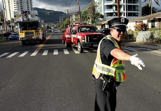 <p>A police officer directs a fire truck to the Marco Polo apartment building after a fire broke out in it in Honolulu, Hawaii, July 14, 2017. (Photo: Hugh Gentry/Reuters) </p>