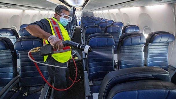 PHOTO: In this July 9, 2020, file photo, cleaning supervisor Jose Mendoza uses an electrostatic sprayer to disinfect the cabin area of a United Airlines 737 jet before passengers are allowed to board at LAX in Los Angeles. (Mel Melcon/Los Angeles Times via Getty Images, FILE)