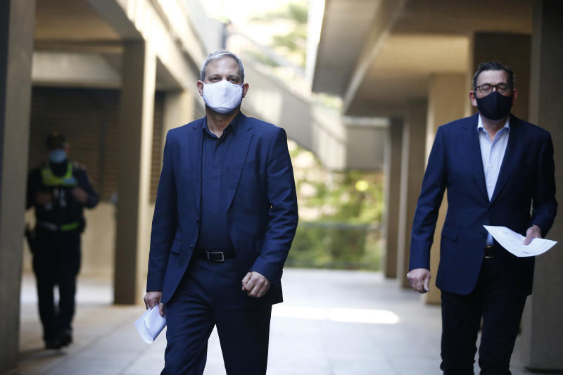 Pictured are Victoria Chief Health Officer Brett Sutton and Victorian Premier Daniel Andrews walking to a briefing wearing face masks.