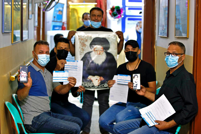 Followers of Shiite cleric Muqtada al-Sadr, pose for a photo holding pictures of him and his father and their vaccination cards as they wait to receive a Chinese Sinopharm vaccine at a clinic in Sadr City, Baghdad, Iraq, Wednesday, May 4, 2021. Iraq's vaccine rollout had been faltering for weeks. Apathy, fear and rumors kept many from getting vaccinated despite a serious surge in coronavirus infections and calls by the government for people to register for shots. It took al-Sadr's public endorsement of vaccinations — and images of him getting the shot — to turn things around. (AP Photo/Hadi Mizban)