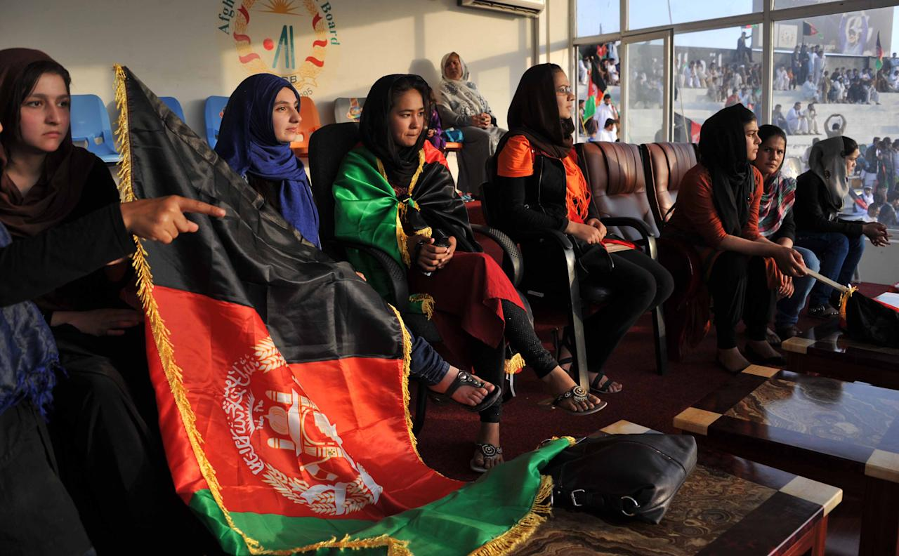 Afghan female cricket fans wait for the arrival of the national team in Kabul on October 12, 2013. Afghanistan's cricket team received a heroes' welcome as cheering crowds lined the streets and packed a stadium in Kabul to greet the players after they qualified for the 2015 World Cup. AFP PHOTO/ Noorullah SHIRZADA        (Photo credit should read Noorullah Shirzada/AFP/Getty Images)