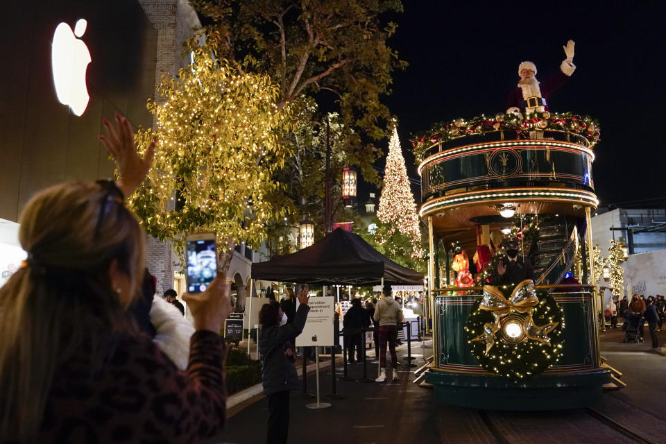 Santa Claus waves to shoppers from a safe distance at the top level of a trolly at The Grove shopping center in Los Angeles on Dec. 3, 2020. Santa visits were canceled due to the spread of COVID-19. In this socially distant holiday season, Santa Claus is still coming to towns (and shopping malls) across America but with a few 2020 rules in effect. (AP Photo/Ashley Landis)