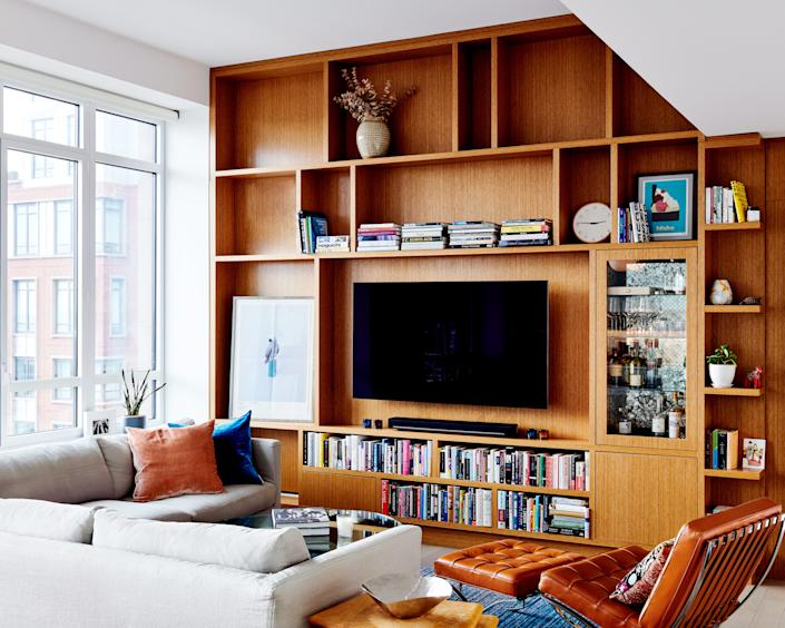 """<div class=""""caption""""> Floor-to-ceiling bookshelves make this home feel full of height and space to breathe. </div>"""