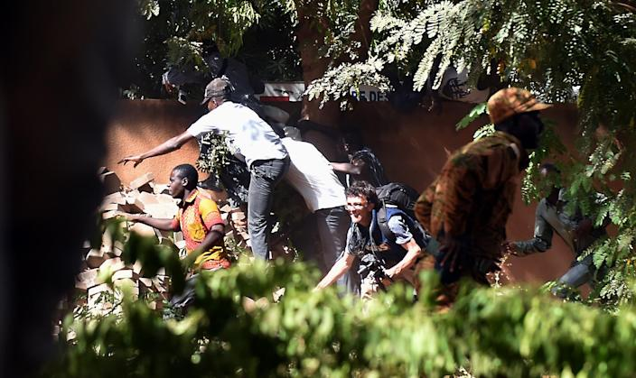 Journalists flee the national television headquarters in Burkina Faso's capital Ouagadougou as gunshots are fired around the premises on November 2, 2014 (AFP Photo/Issouf Sanogo)