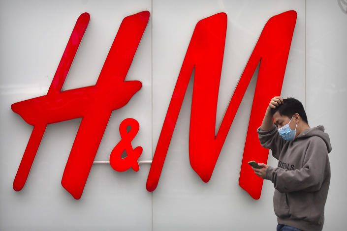 A man uses his smartphone as he walks past an H&M clothing store at a shopping mall in Beijing, Friday, March 26, 2021. H&M disappeared from the internet in China as the government raised pressure on shoe and clothing brands and announced sanctions Friday against British officials in a spiraling fight over complaints of abuses in the Xinjiang region. (AP Photo/Mark Schiefelbein)