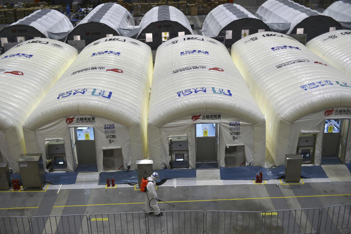 A worker disinfects the flooring outside the inflated cabins at the pop-up Huo-Yan Laboratory set up in an expo center to test samples for covid-19 virus in Nanjing in east China's Jiangsu province Wednesday, July 28, 2021. China's worst coronavirus outbreak since the start of the pandemic a year and a half ago escalated Wednesday, Aug. 4, 2021, with dozens more cases around the country, the sealing-off of one city and the punishment of its local leaders. (Chinatopix Via AP)