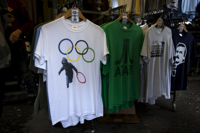 <p> In this photo taken Monday, July 16, 2012, a t-shirt depicting a rioter holding an Olympic ring is displayed on sale in a London market. The guardians of the games are vigilant about protecting the integrity - and the commercial clout - of the Olympic brand. But even they can't stop the irreverent spirit of artists and craftspeople, who have responded to the games with a cheeky mix of celebration, skepticism and satire. (AP Photo/Matt Dunham) </p>