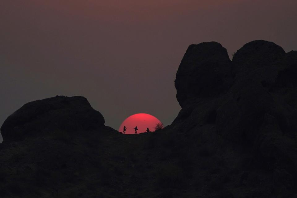 Hikers pause to watch the sunset at Papago Park during a heatwave where temperatures reached 115-degrees Tuesday, June 15, 2021, in Phoenix. (AP Photo/Ross D. Franklin)