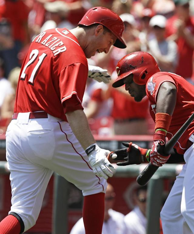 Cincinnati Reds' Todd Frazier (21) is congratulated by Brandon Phillips after Frazier hit a solo home run off San Francisco Giants starting pitcher Madison Bumgarner in the first inning of a baseball game, Thursday, June 5, 2014, in Cincinnati. (AP Photo/Al Behrman)