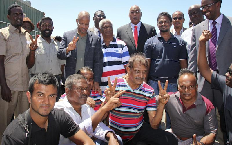 Crew members from the Aris 13 oil tanker, pose for a photo with visiting Somali officials after they were released by pirates after negotiations by officials and local elders, in Bossaso, in Somalia's semiautonomous northeastern state of Puntland Sunday, March 19, 2017. The captain of the tanker Nicholas Anthony said Sunday he is grateful for efforts by the semiautonomous Puntland state in northern Somalia to secure their release. (AP Photo)