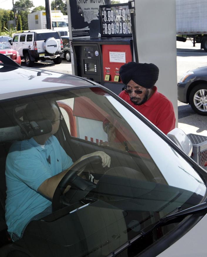 Lukoil service station worker Harbhasan Singh explains to a customer Wednesday, Sept. 12, 2012, in South Plainfield, N.J., that as a protest to what they say are unfair pricing practices by Lukoil North America, the station has raised their gas price to more than $8 a gallon. More than 50 Lukoil gas stations in New Jersey and Pennsylvania were jacking up prices to more than $8 a gallon Wednesday to protest what they say are unfair pricing practices by Lukoil North America that they say leave them at a competitive disadvantage. (AP Photo/Mel Evans)