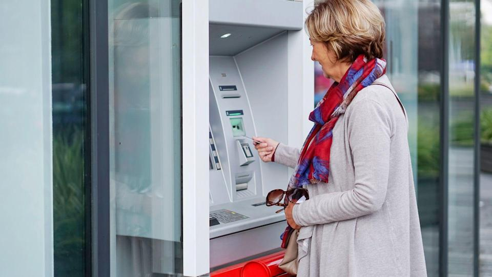 Senior woman using ATM in the city.