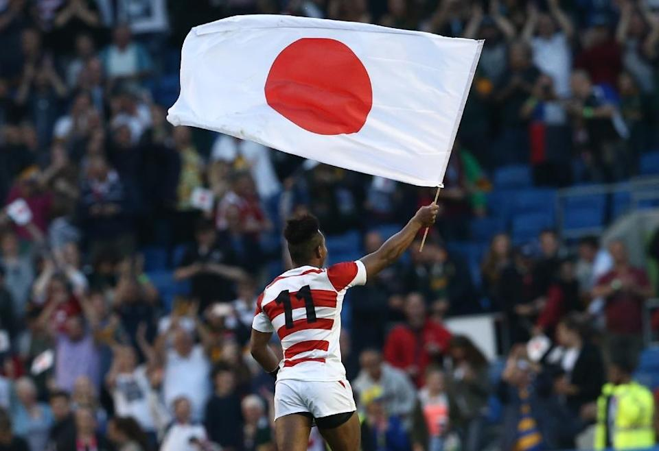 Kotaro Matsushima waves the Japanese national flag as the team celebrate their victory in the Pool B match of the 2015 Rugby World Cup against South Africa in Brighton, England on September 19, 2015 (AFP Photo/Justin Tallis)