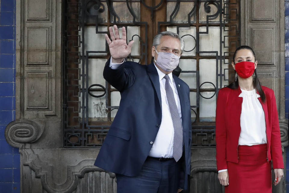 Argentine President Alberto Fernandez waves as he leaves the Old Town Hall with Mexico City Mayor Claudia Sheinbaum, in Mexico City, Tuesday, Feb. 23, 2021. Fernandez is on an official visit to Mexico.(AP Photo/Rebecca Blackwell)