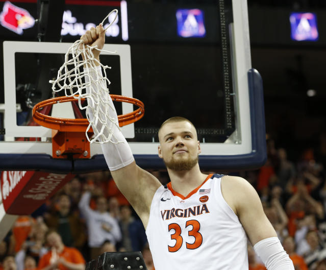 Virginia center Jack Salt (33) holds the net after a victory over Louisville after an NCAA college basketball game in Charlottesville, Va., Saturday, March 9, 2019. (AP Photo/Steve Helber)